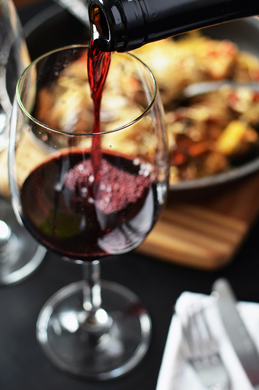 Wine poured on glass with a meal on the background