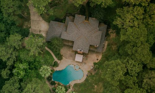 Aerial view of secluded house with a pool